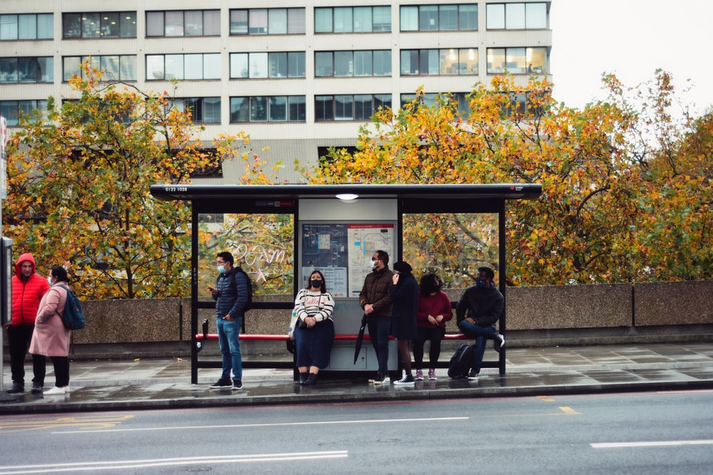 people sitting on bench in front of building during daytime