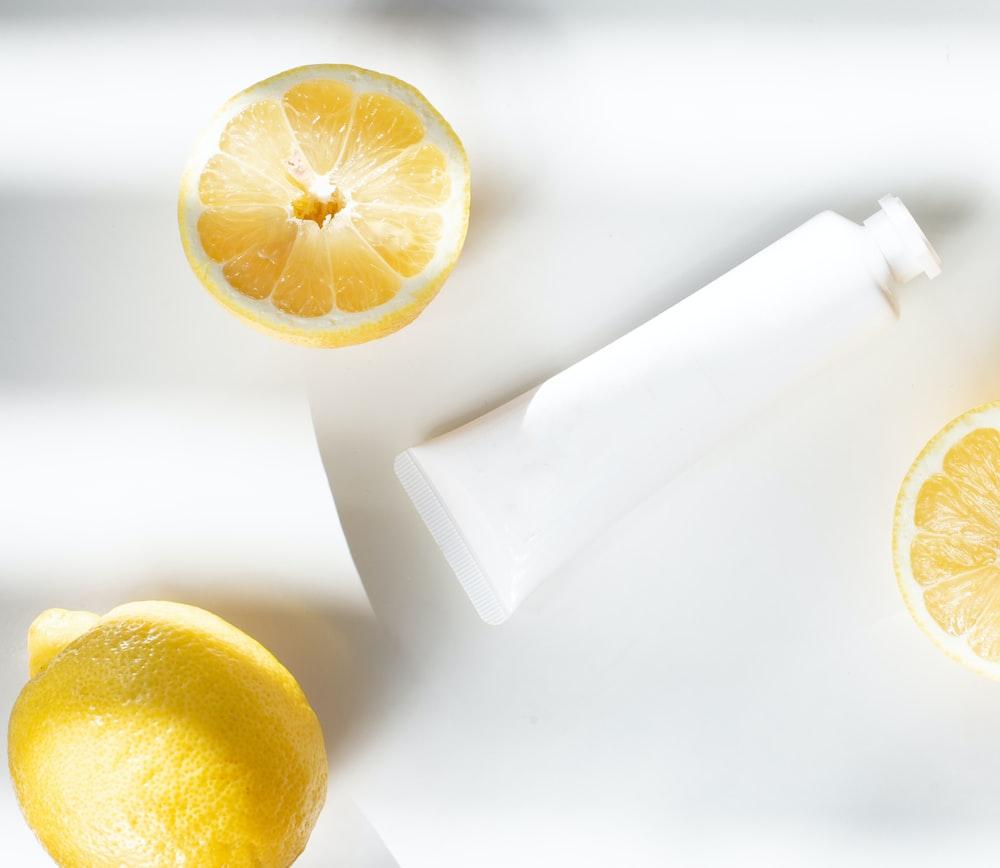 sliced lemon beside white ceramic container
