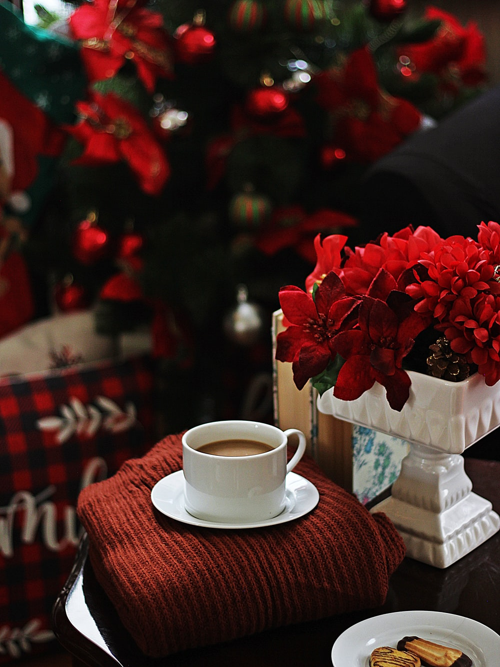red roses on white ceramic teacup on red and white checkered table cloth