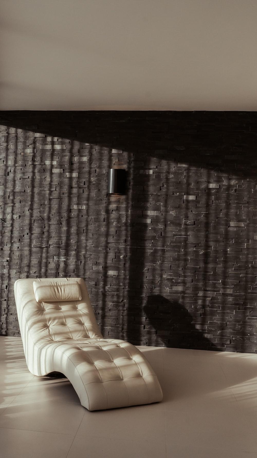 white and brown sofa near brown curtain