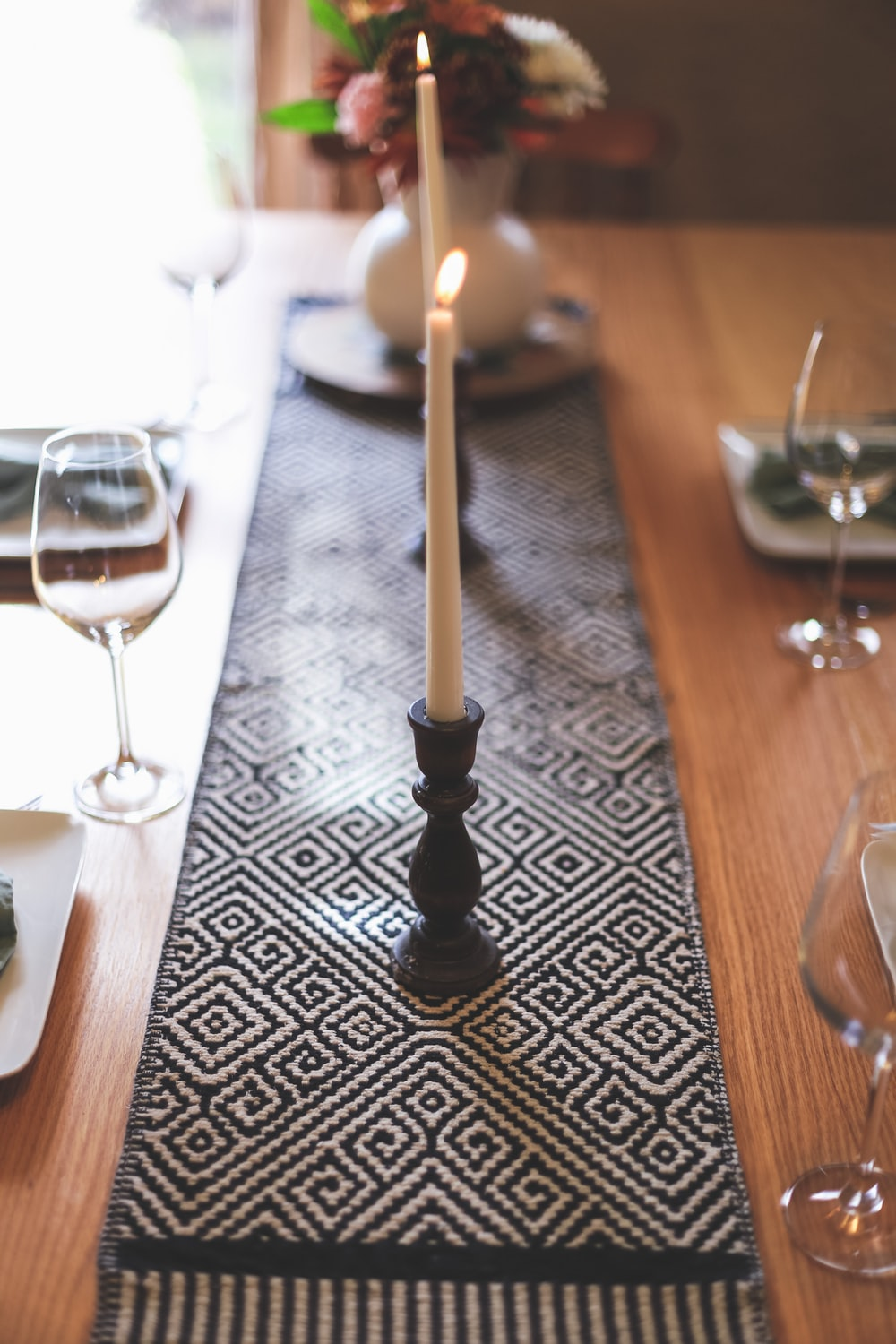 black candle holder with white candle on brown wooden table