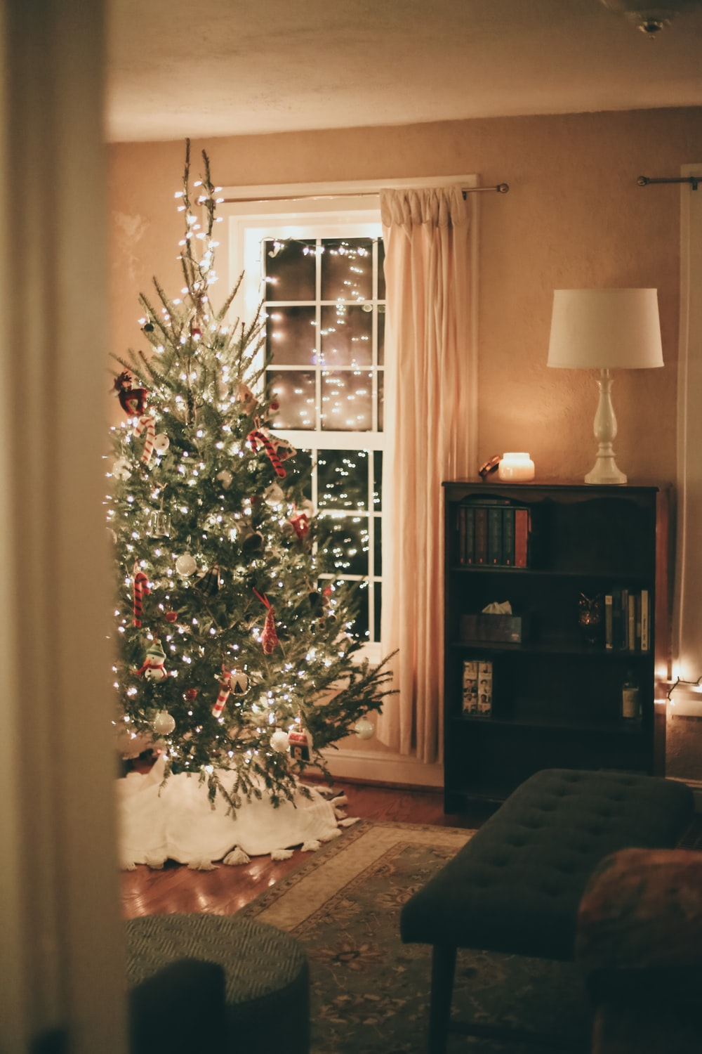 green christmas tree with baubles near brown wooden shelf