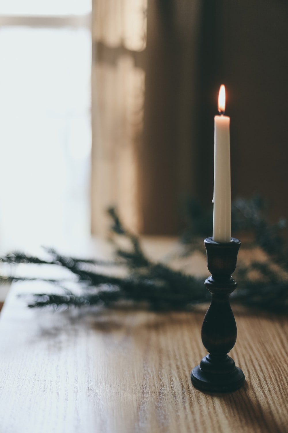 white candle on black candle holder