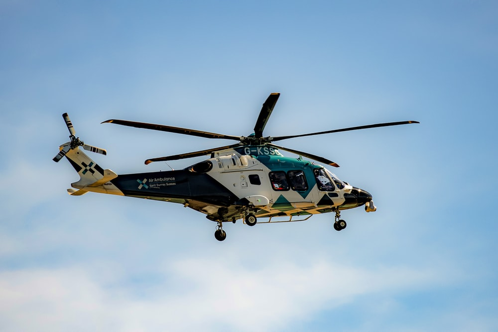 yellow and black helicopter flying in the sky during daytime