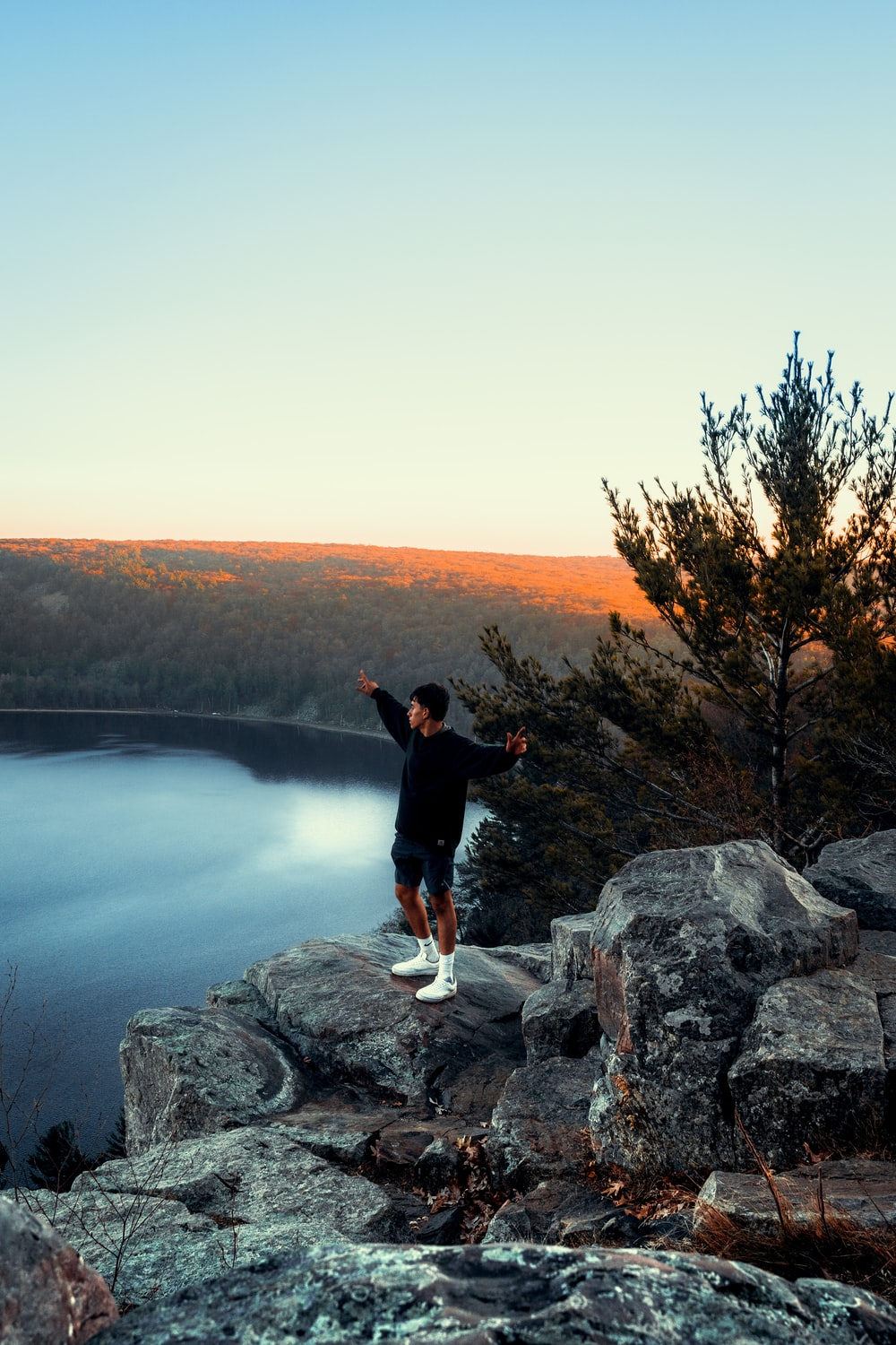 man in black jacket standing on gray rock near body of water during daytime