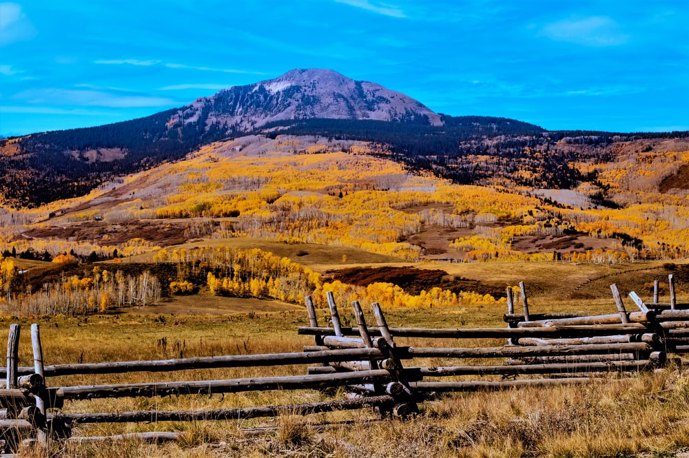 brown wooden fence on brown grass field near mountain under blue sky during daytime