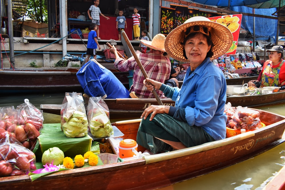 woman in blue dress shirt and brown straw hat sitting on brown wooden boat