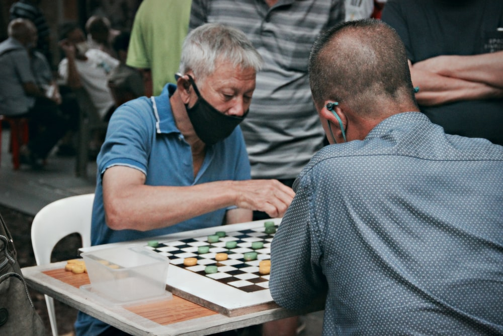 man in blue t-shirt playing chess