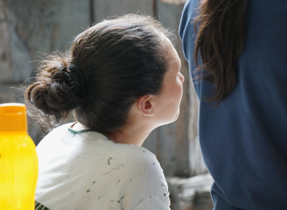 woman in white shirt standing beside woman in blue shirt