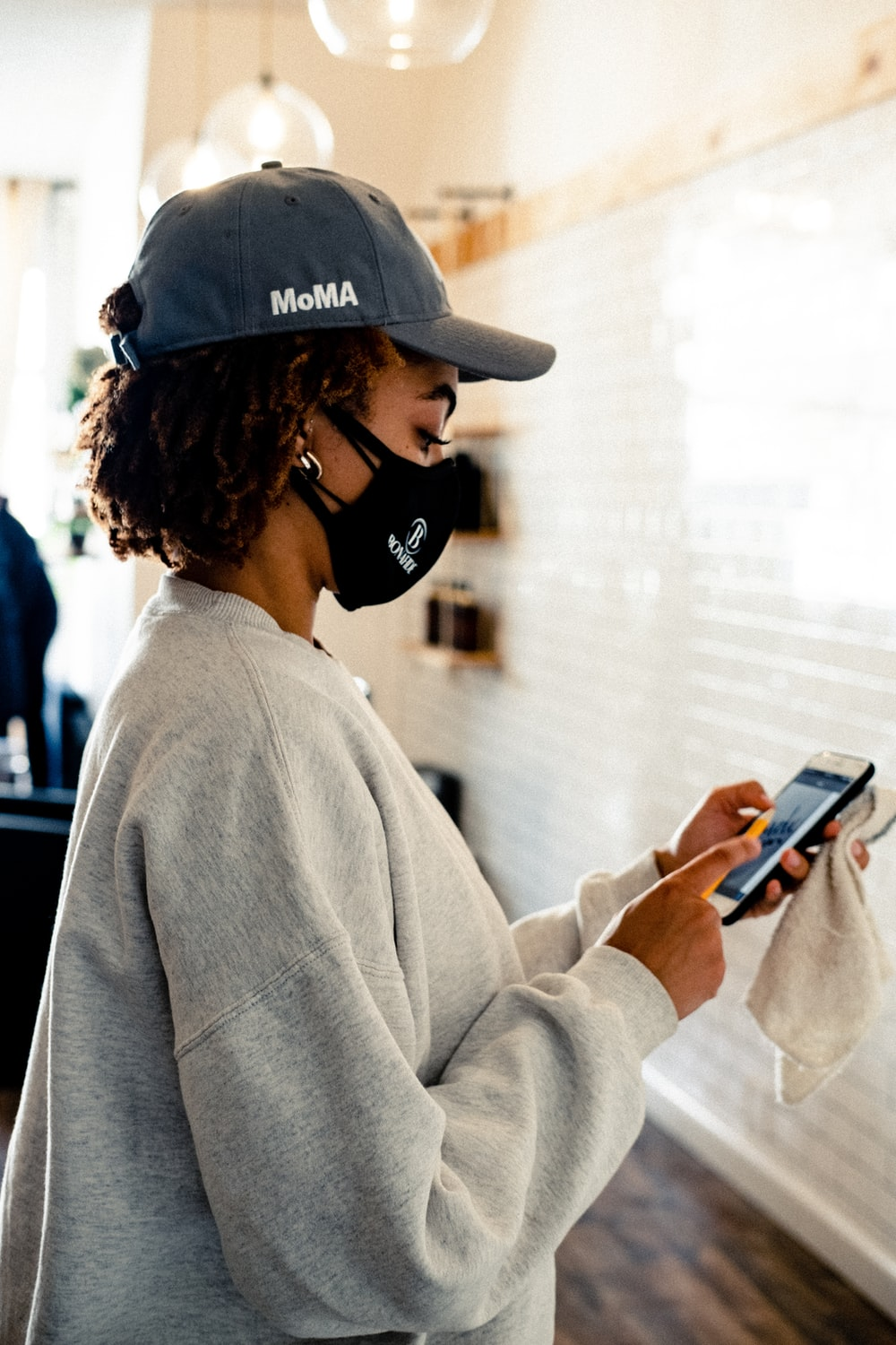 woman in gray sweater holding smartphone