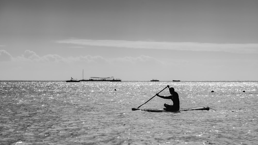 grayscale photo of man riding on boat on sea