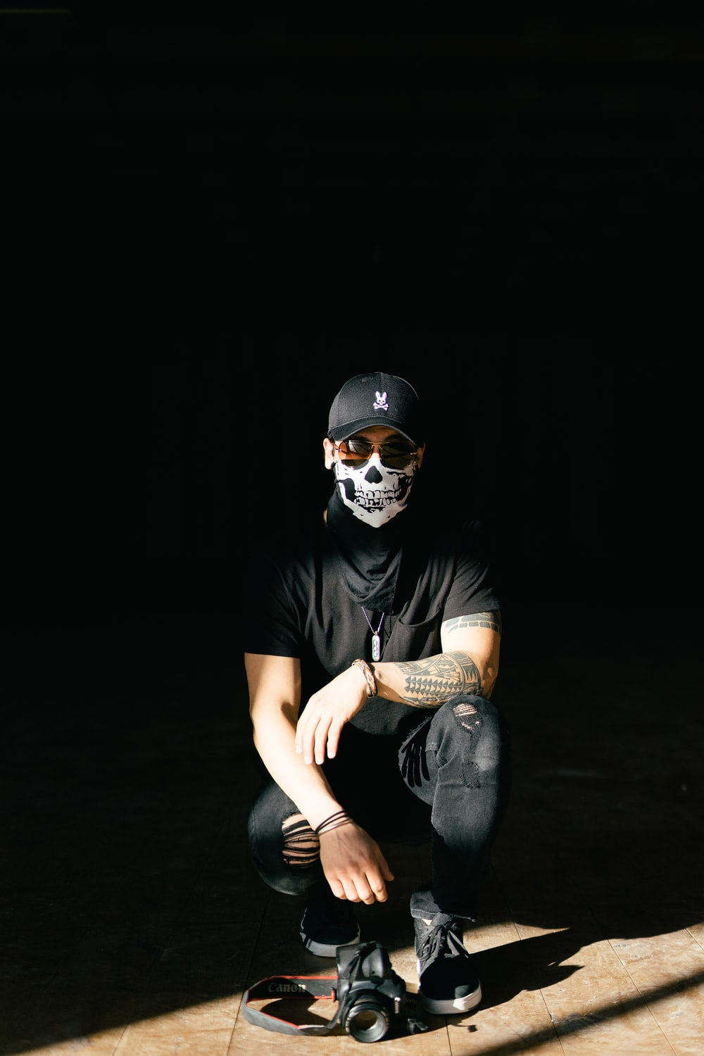 man in black crew neck t-shirt and blue denim jeans wearing white mask
