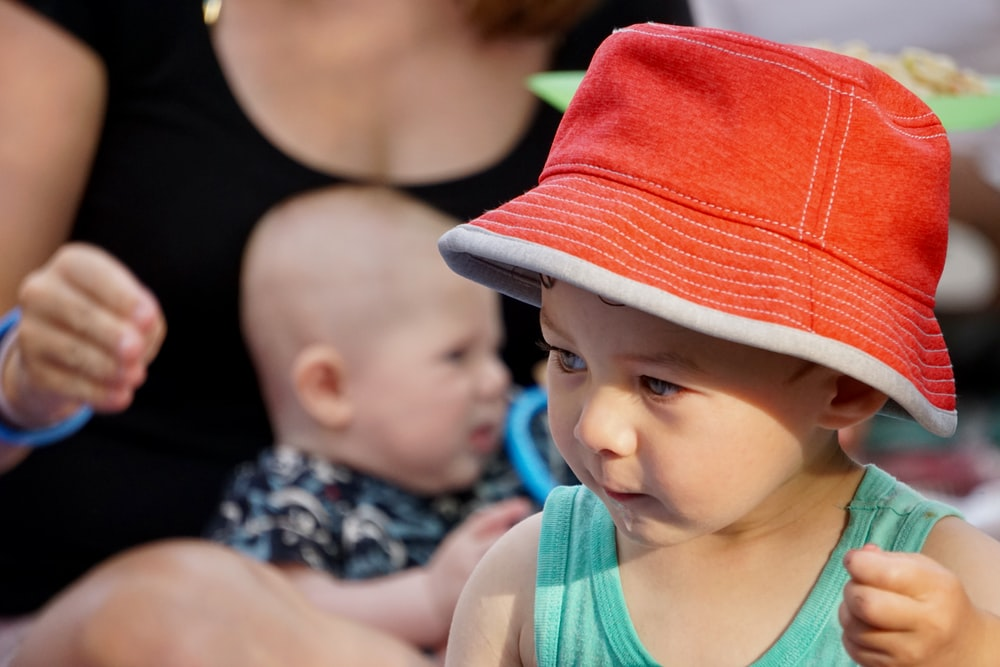 baby in orange hat and blue tank top