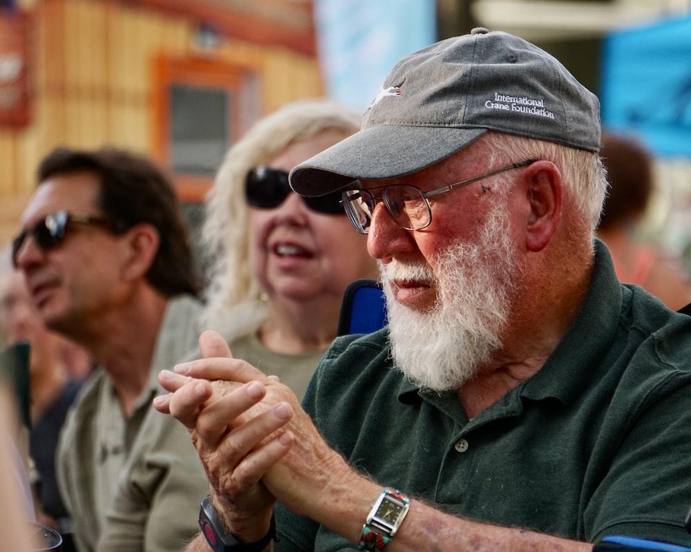 man in black jacket wearing black sunglasses and gray cap
