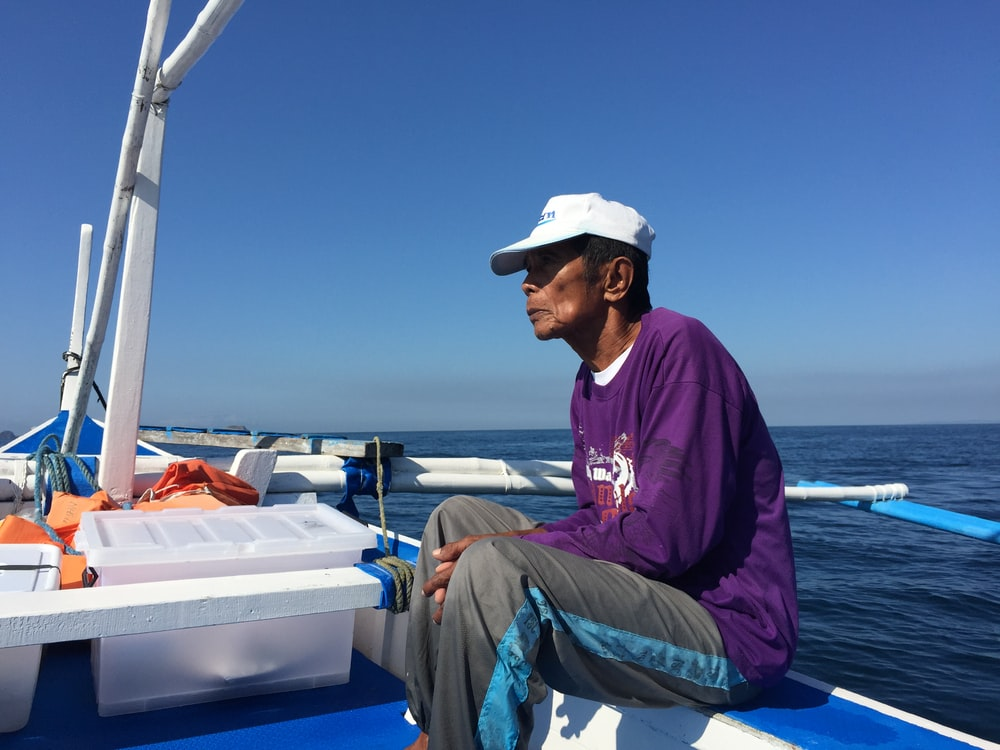 man in purple hoodie and gray pants sitting on boat during daytime