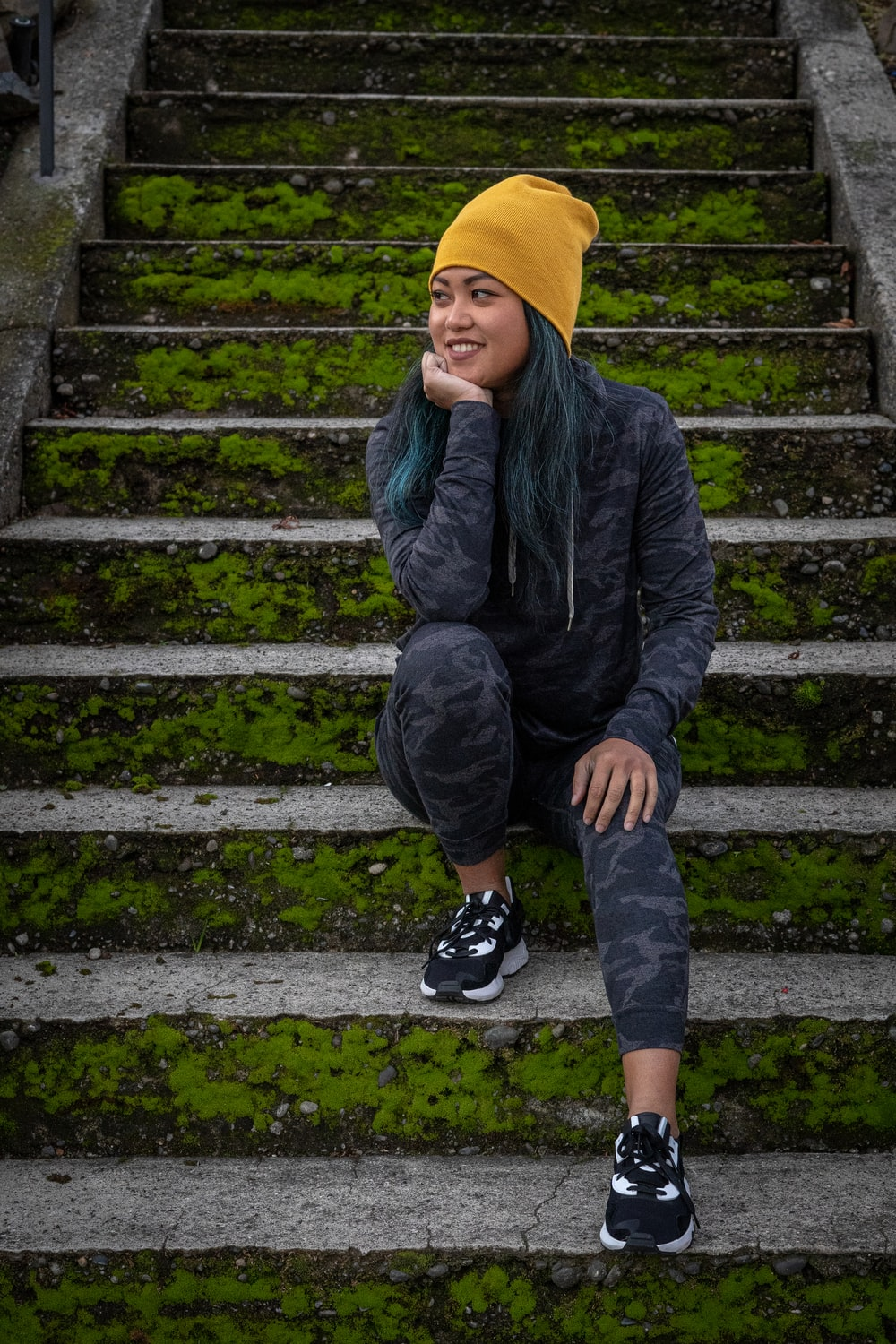 boy in black jacket and yellow knit cap sitting on concrete stairs