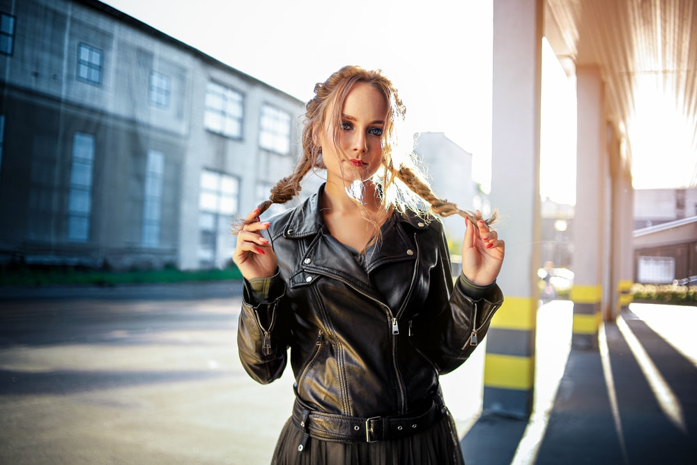 woman in black leather jacket standing on street during daytime