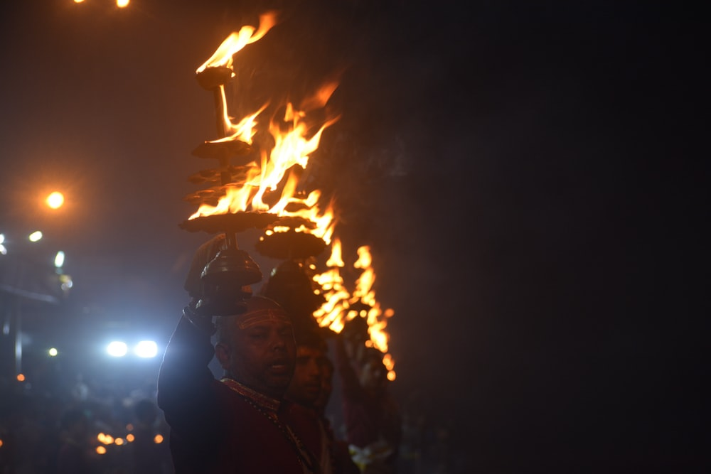 man in brown leather jacket holding fire