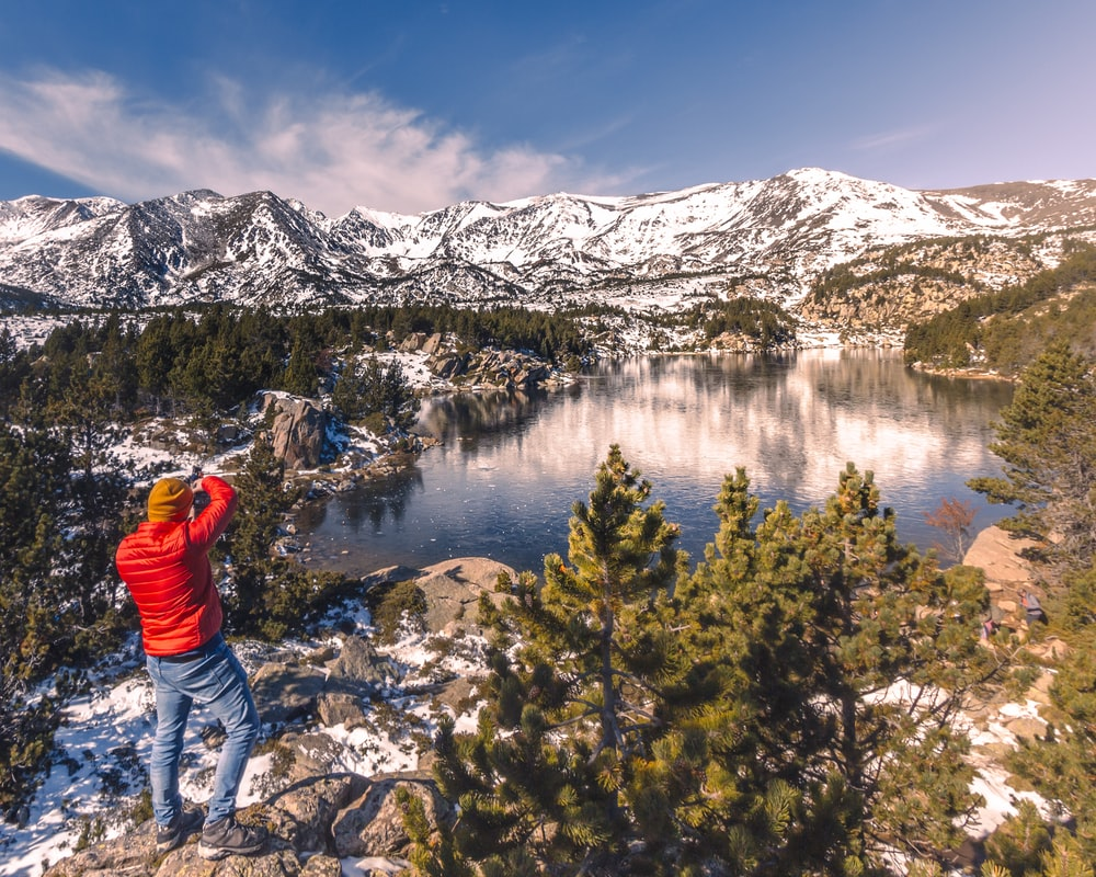 person in red jacket standing on rocky mountain near lake during daytime