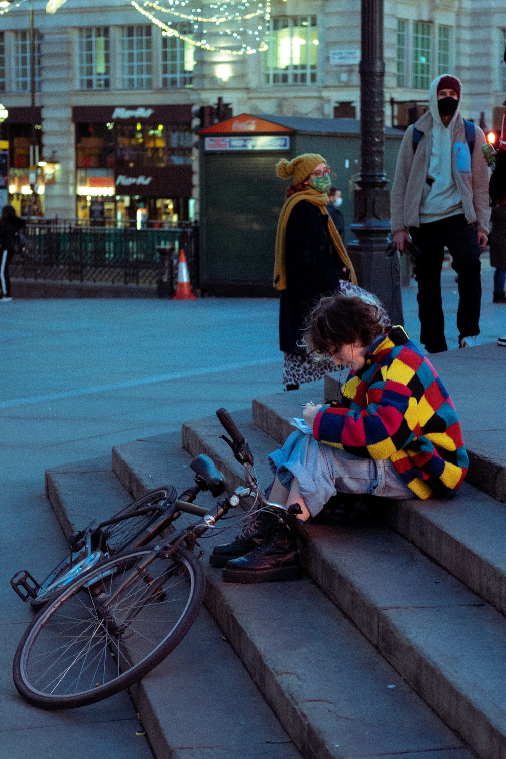 woman in yellow and blue striped long sleeve shirt sitting on gray concrete bench