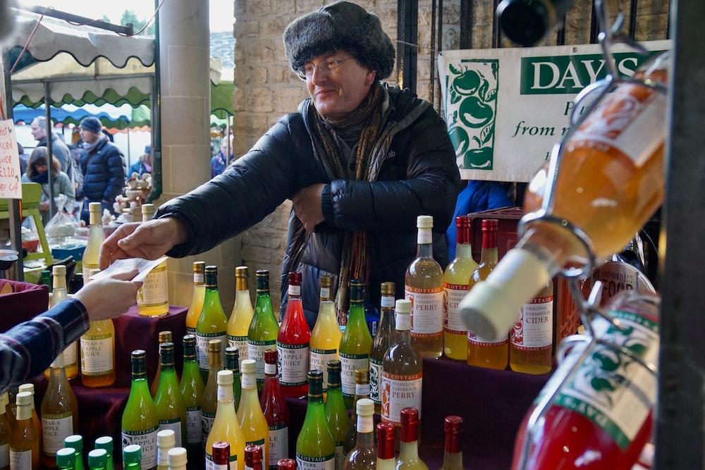 man in black jacket holding bottle