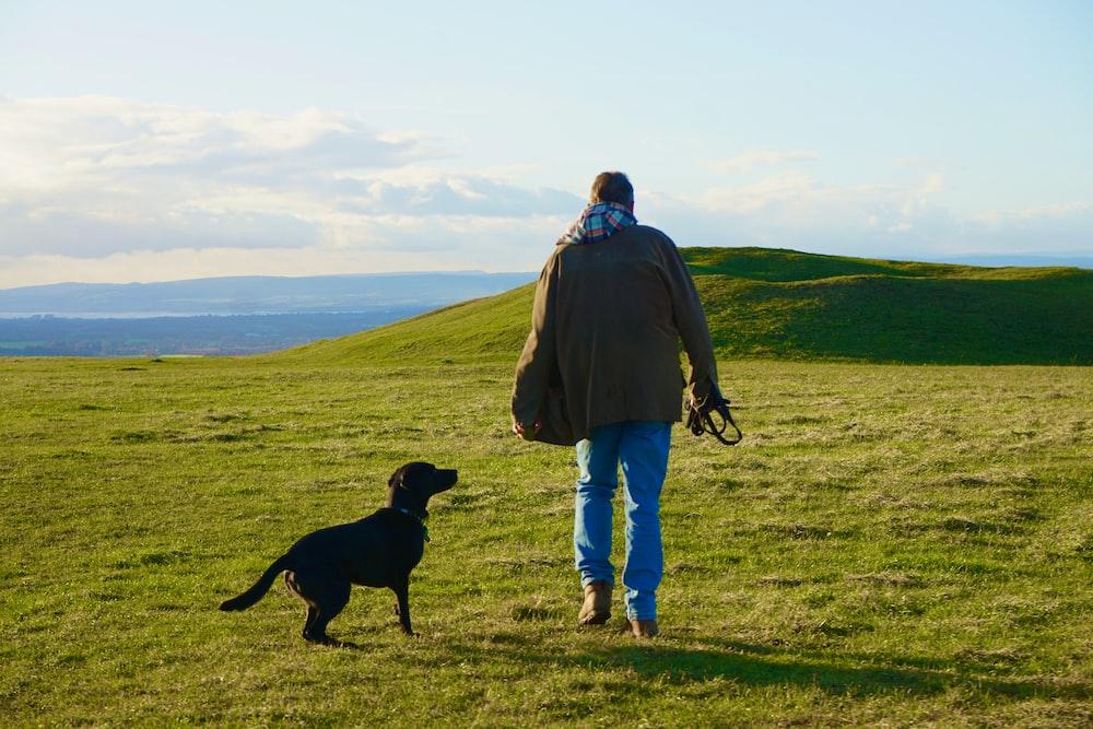 man in blue jacket standing beside black labrador retriever on green grass field during daytime