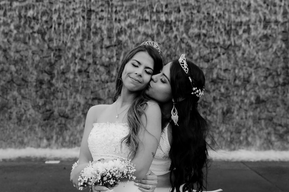 grayscale photo of woman in wedding dress beside woman in wedding dress