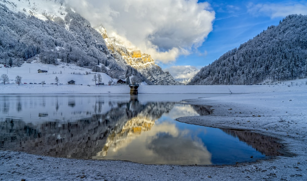 snow covered mountain near body of water during daytime