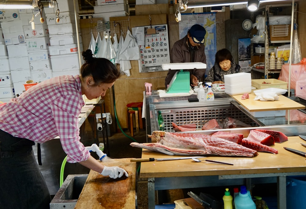 woman in pink and white long sleeve shirt slicing fish