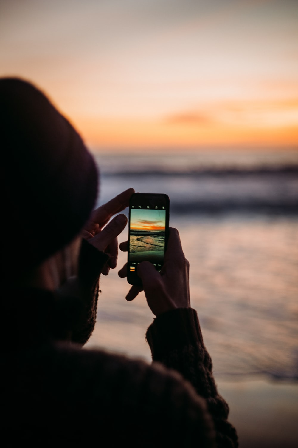 person holding black smartphone during sunset