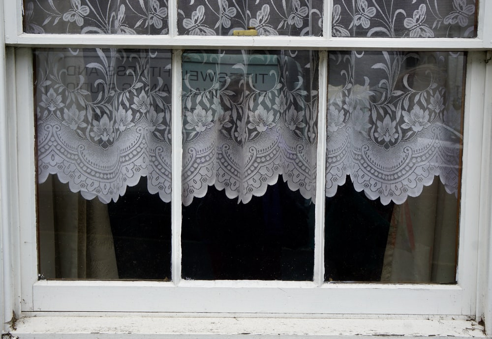 white floral window curtain on window