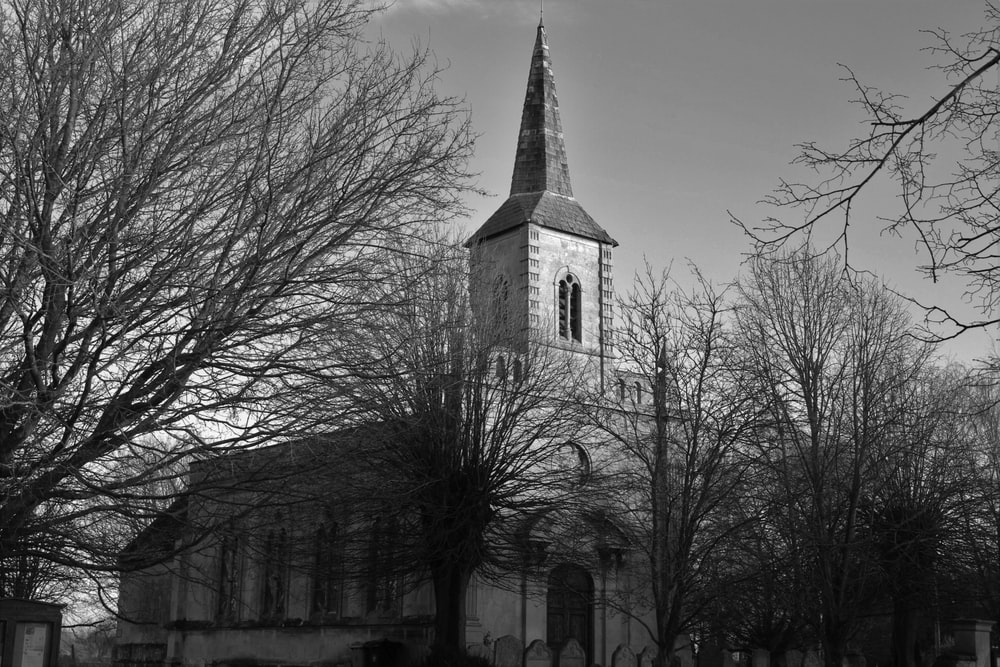 grayscale photo of church near bare trees