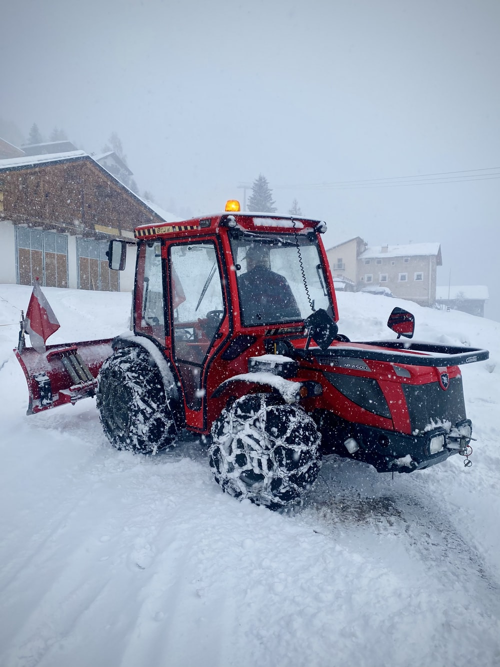 red and black tractor on snow covered ground during daytime
