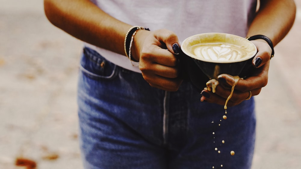 person in blue denim jacket holding white ceramic mug with coffee