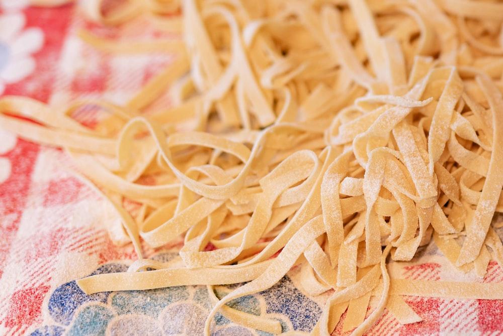 yellow pasta on white and blue textile