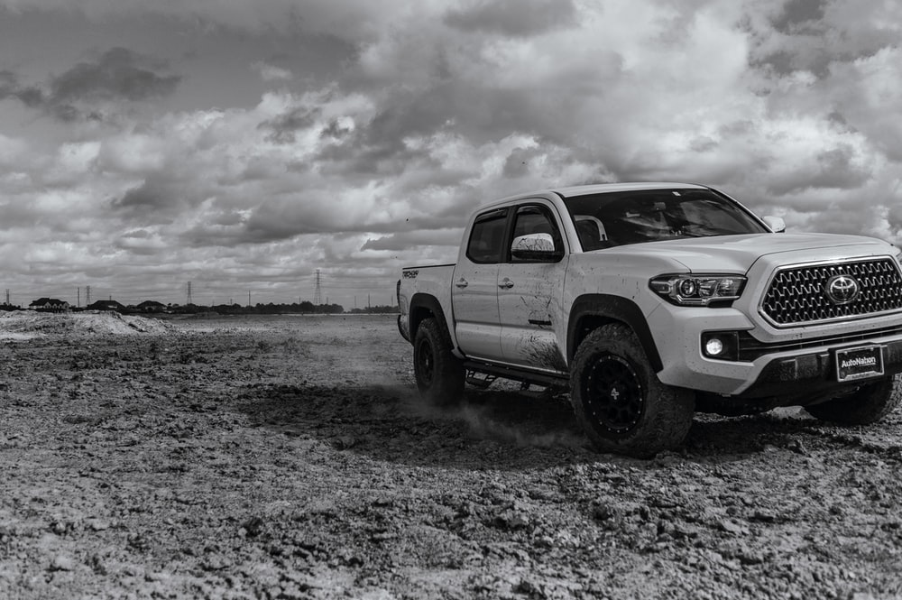 white crew cab pickup truck on gray sand under white clouds during daytime