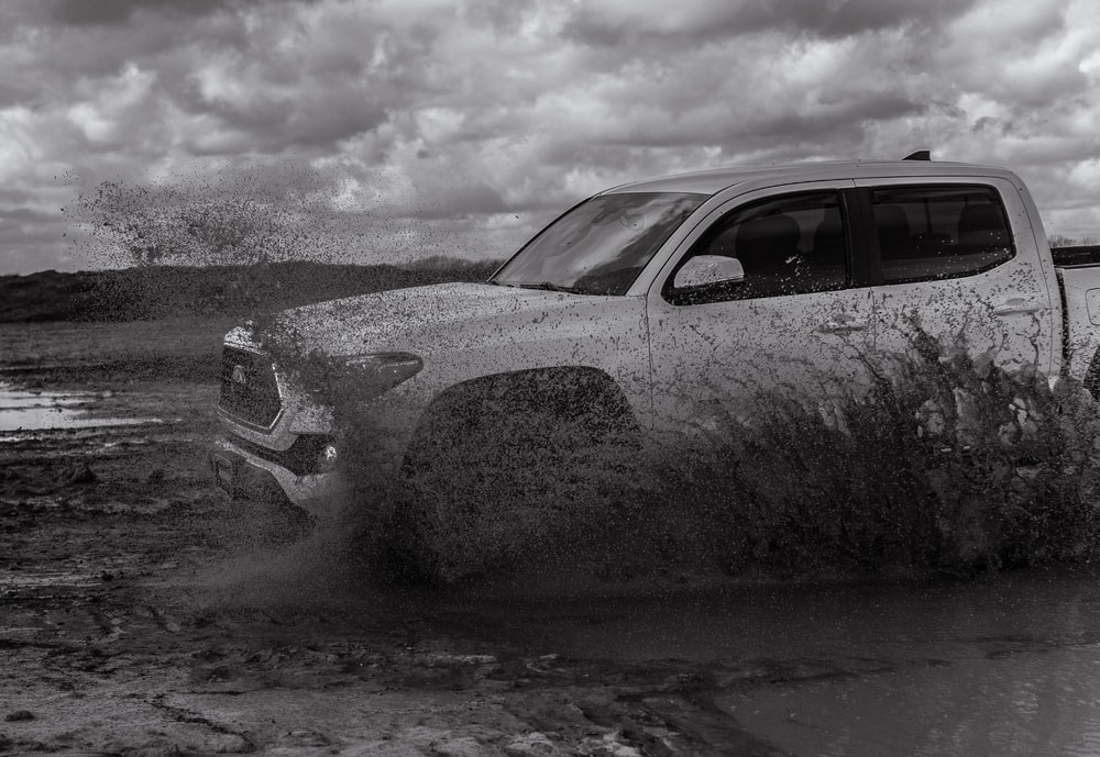 grayscale photo of car covered with snow