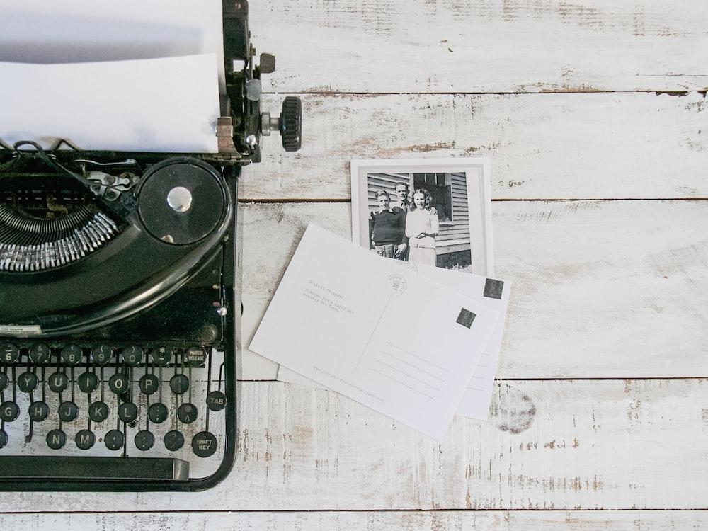 black typewriter beside white printer paper