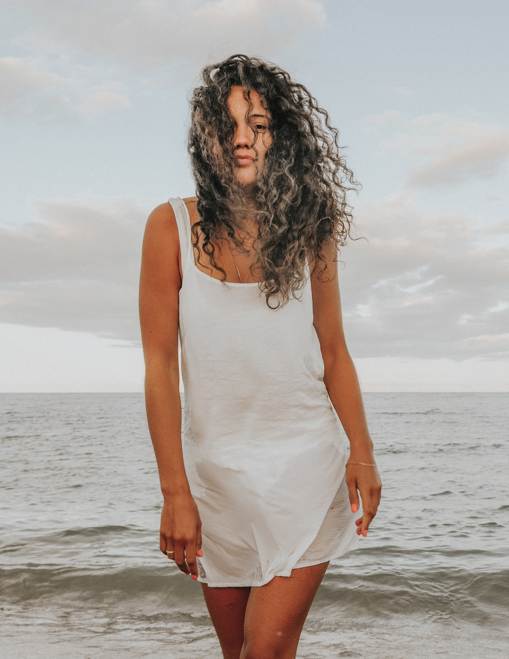 woman in white tank top standing on sea shore during daytime