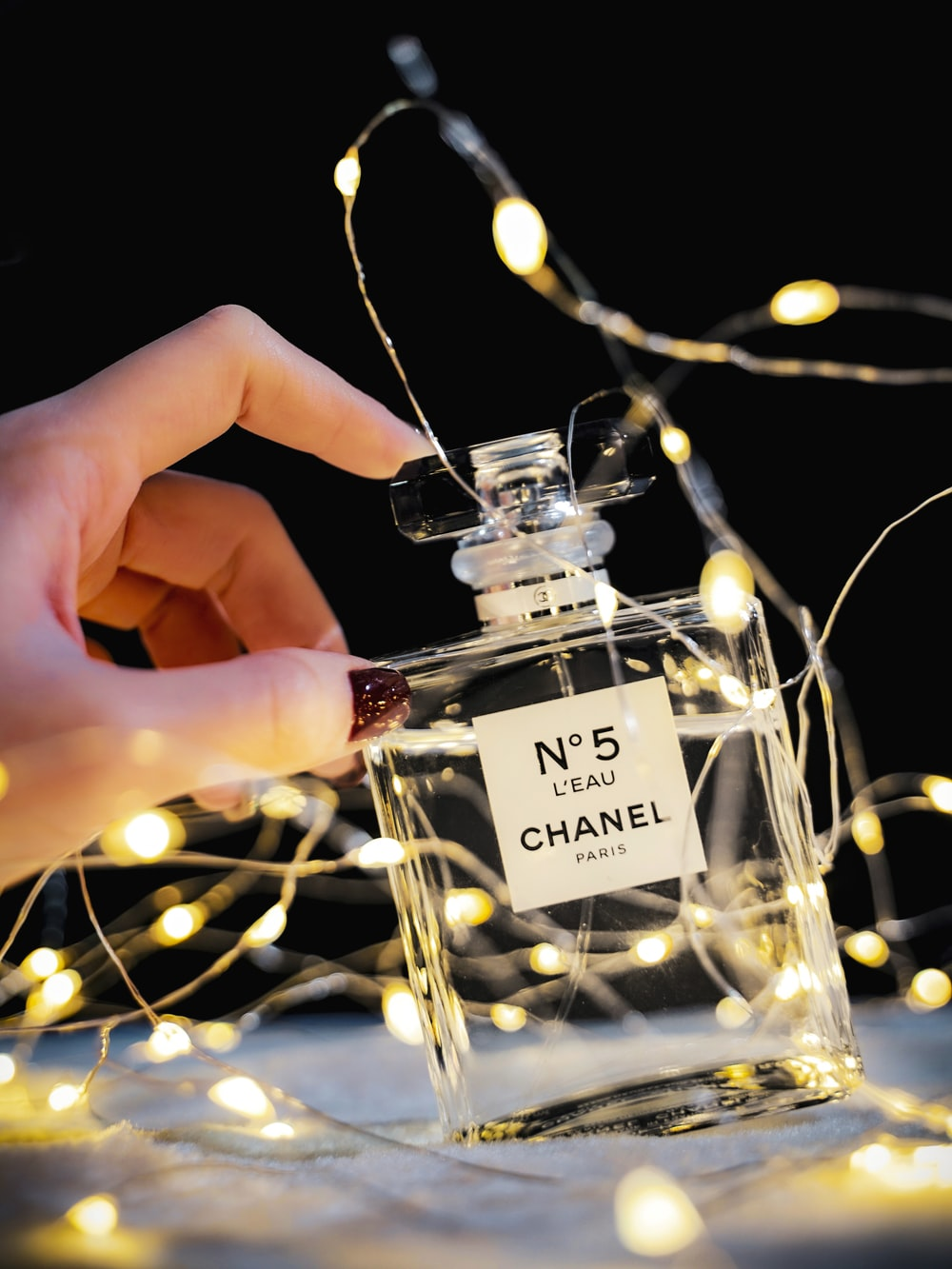 person holding clear glass perfume bottle