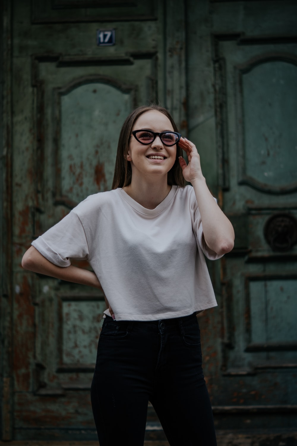 woman in white crew neck t-shirt and black pants wearing red framed eyeglasses