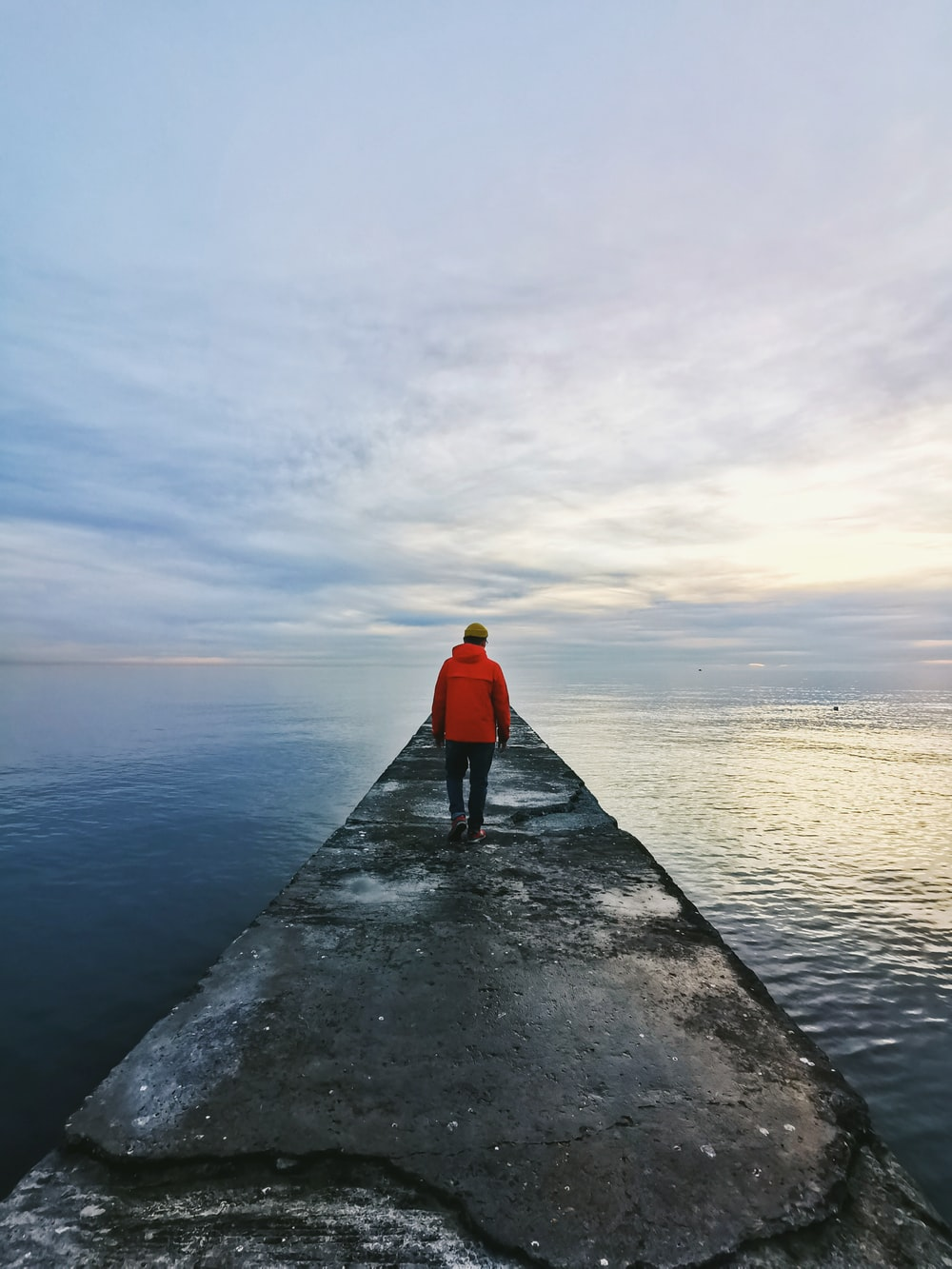man in red hoodie standing on dock near body of water during daytime