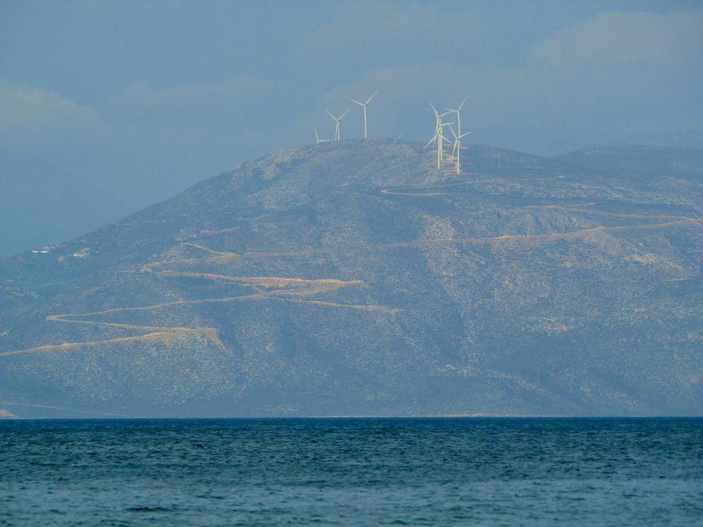 white sailboat on sea near mountain during daytime