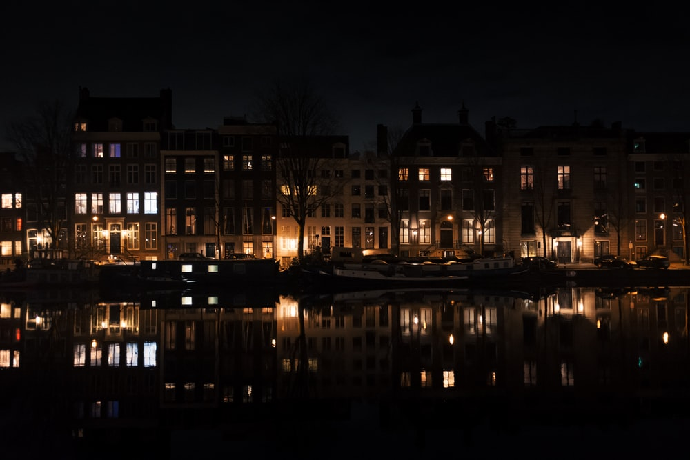 lighted building near body of water during night time