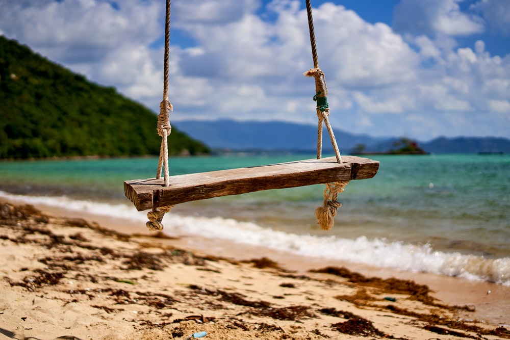 brown wooden swing on brown sand during daytime