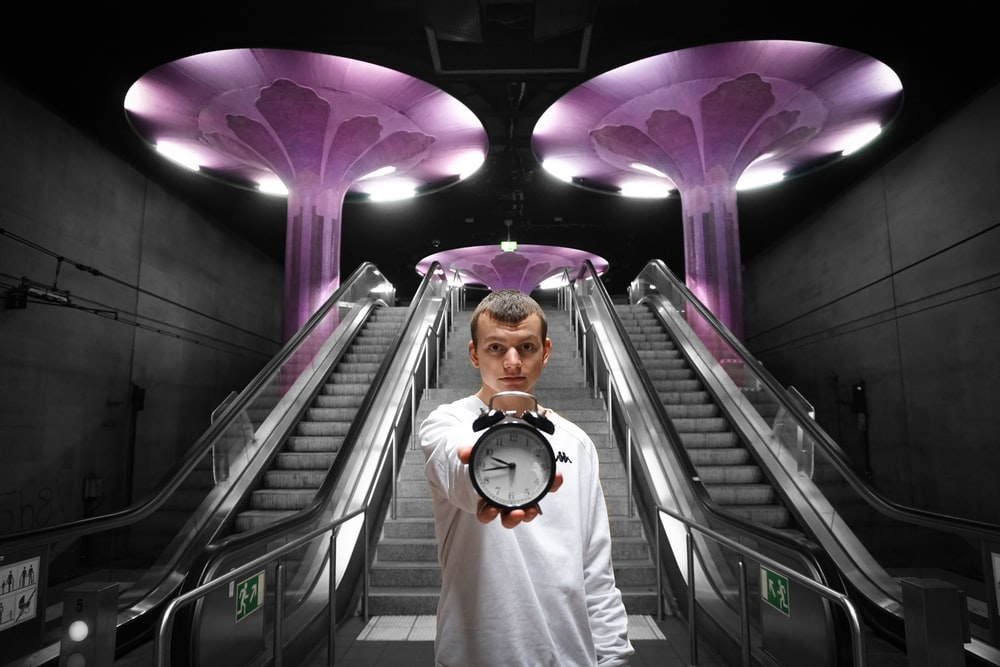 man in white dress shirt standing on escalator