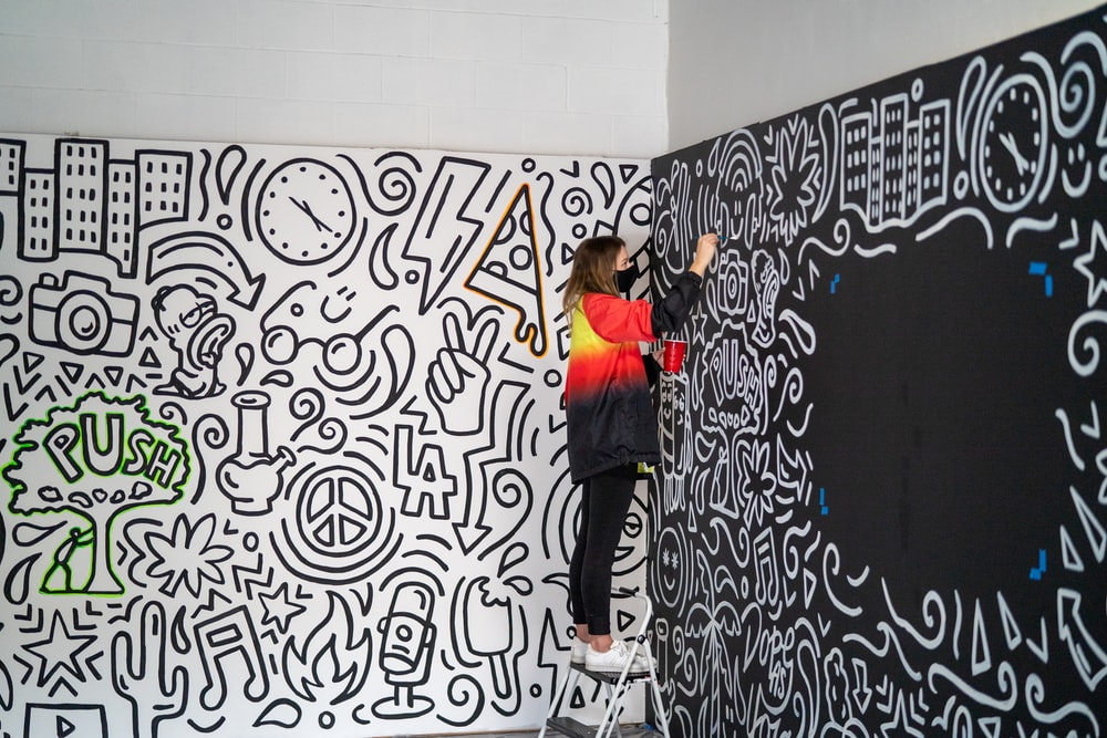 woman in black pants and orange jacket standing beside wall with graffiti