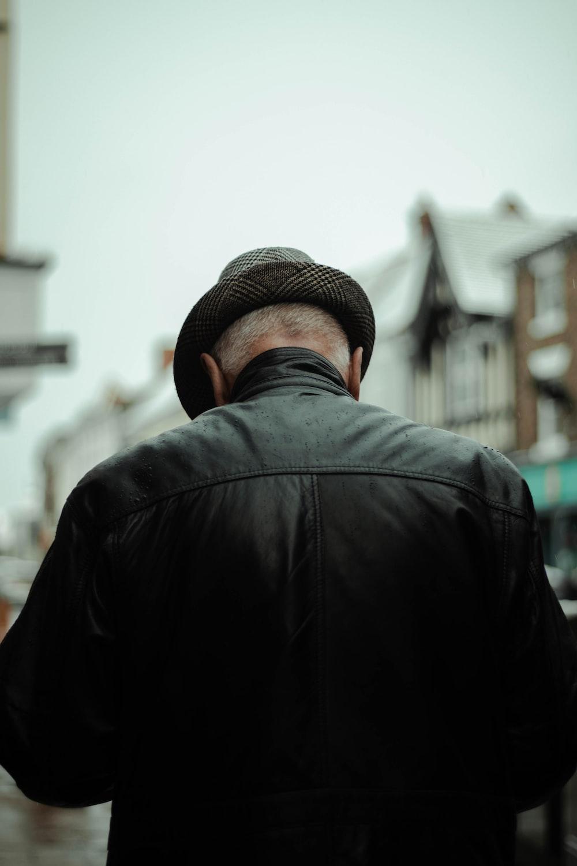 man in black jacket wearing brown fedora hat