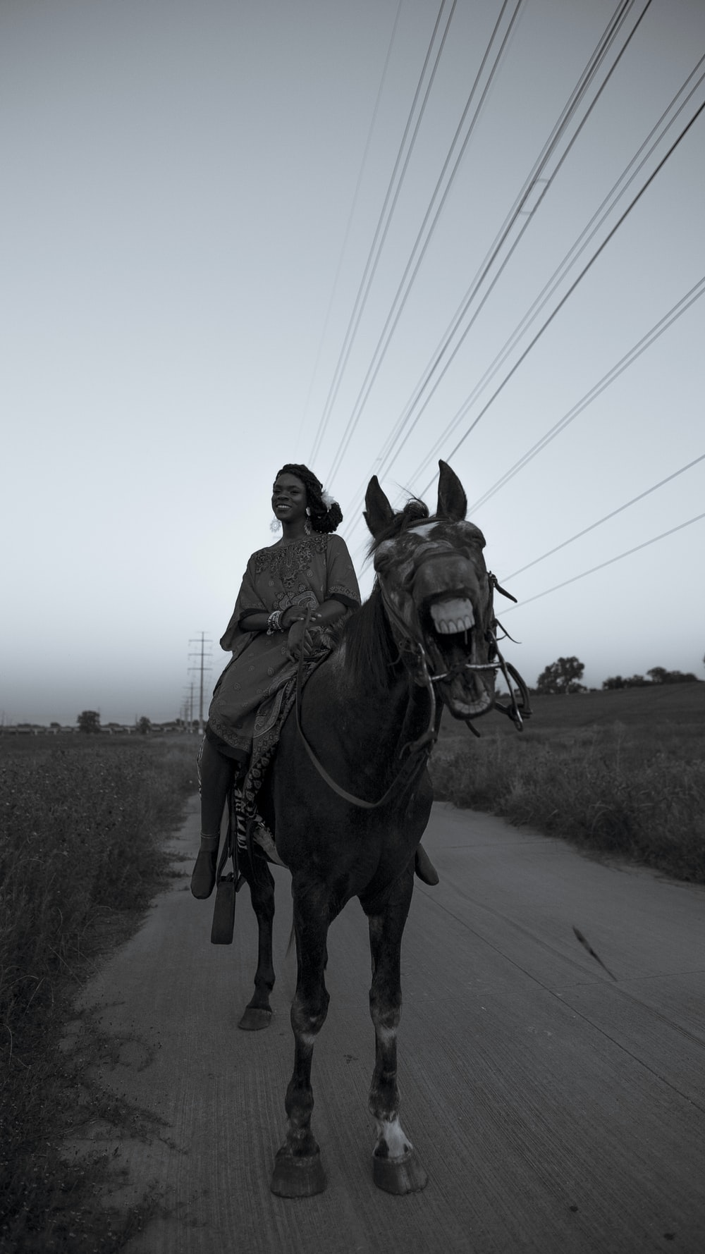 man riding horse on road during daytime