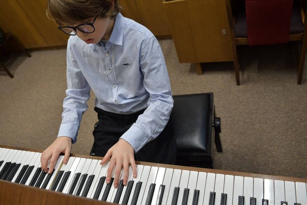 boy in blue denim jacket playing piano